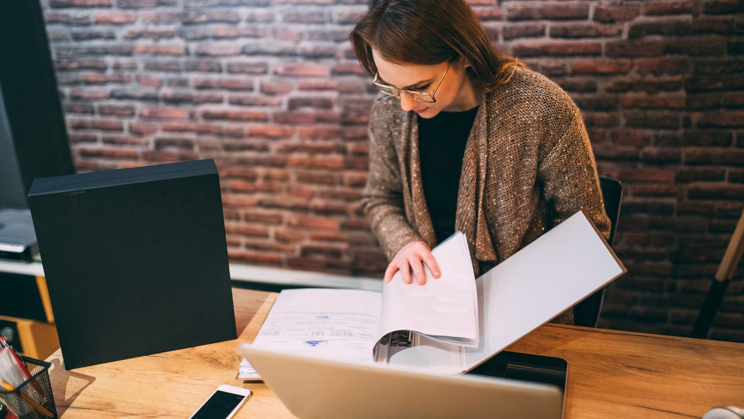 Woman looking through product disclosure statements.