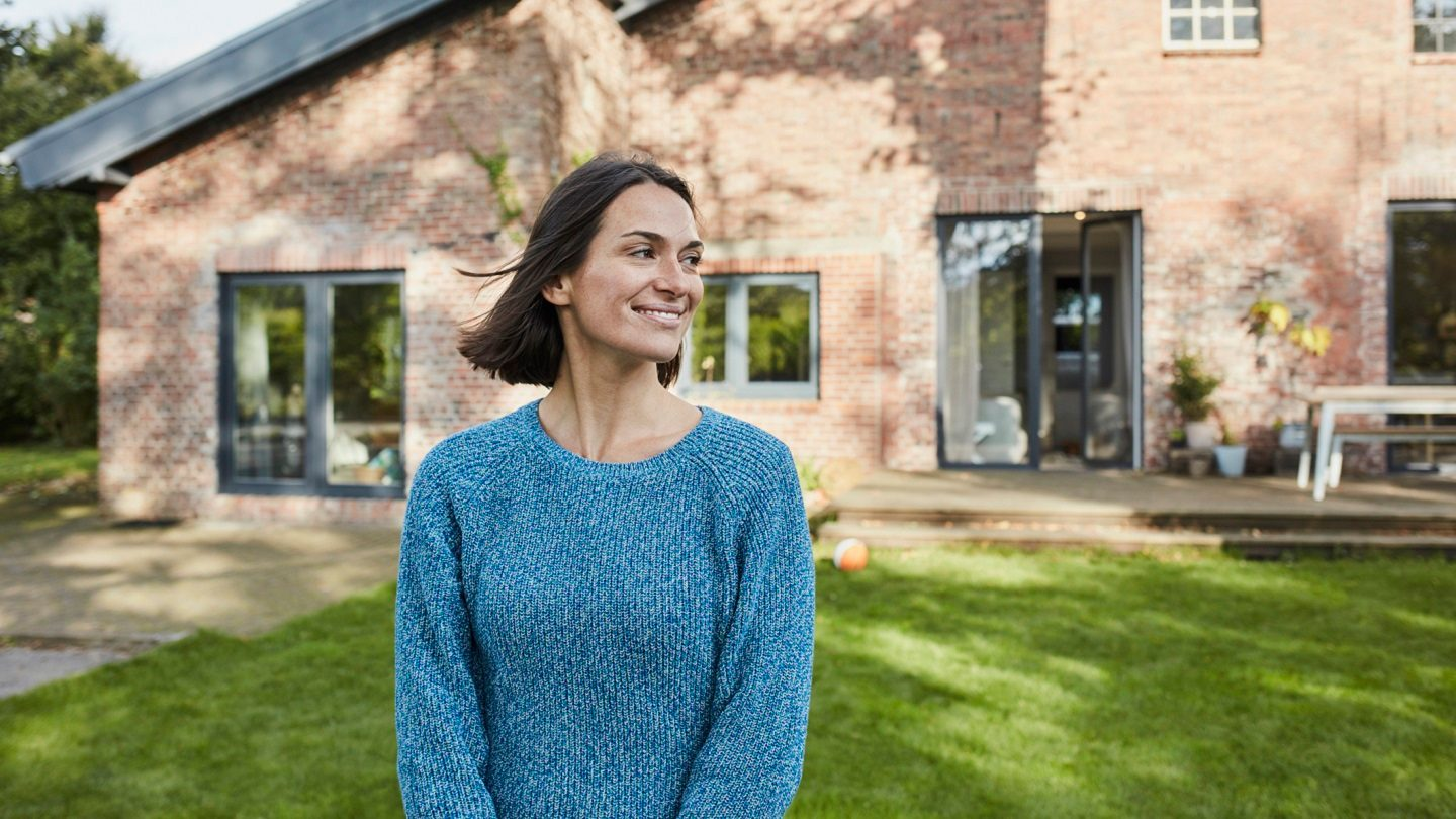 first home buyer standing in front of her property