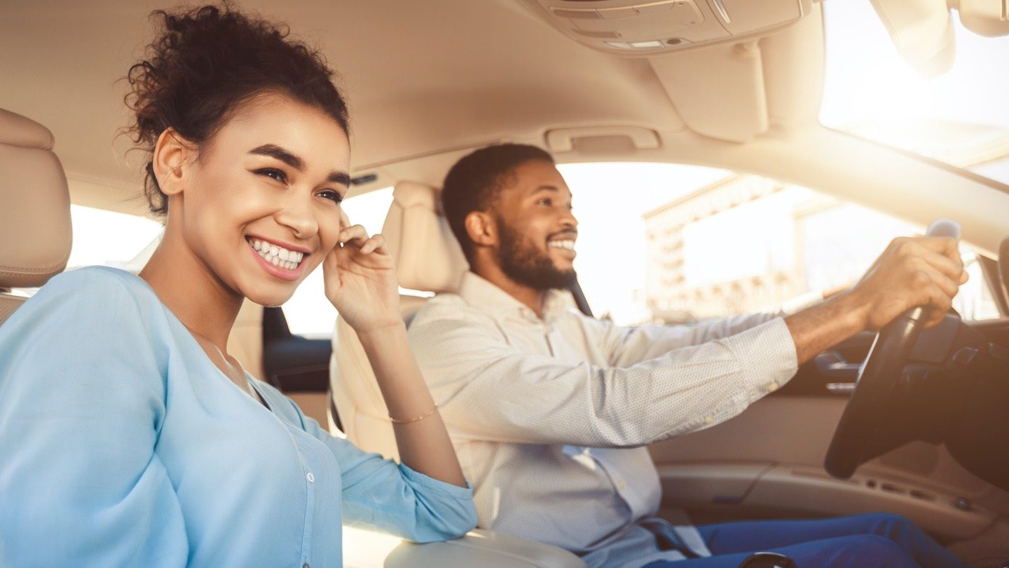 Man and woman driving in car, insured with new Australian car insurer.