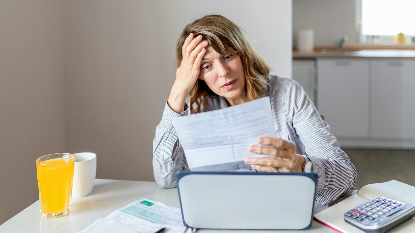 Woman sitting at table with head in hand, looking at bills and worrying about government support ending.