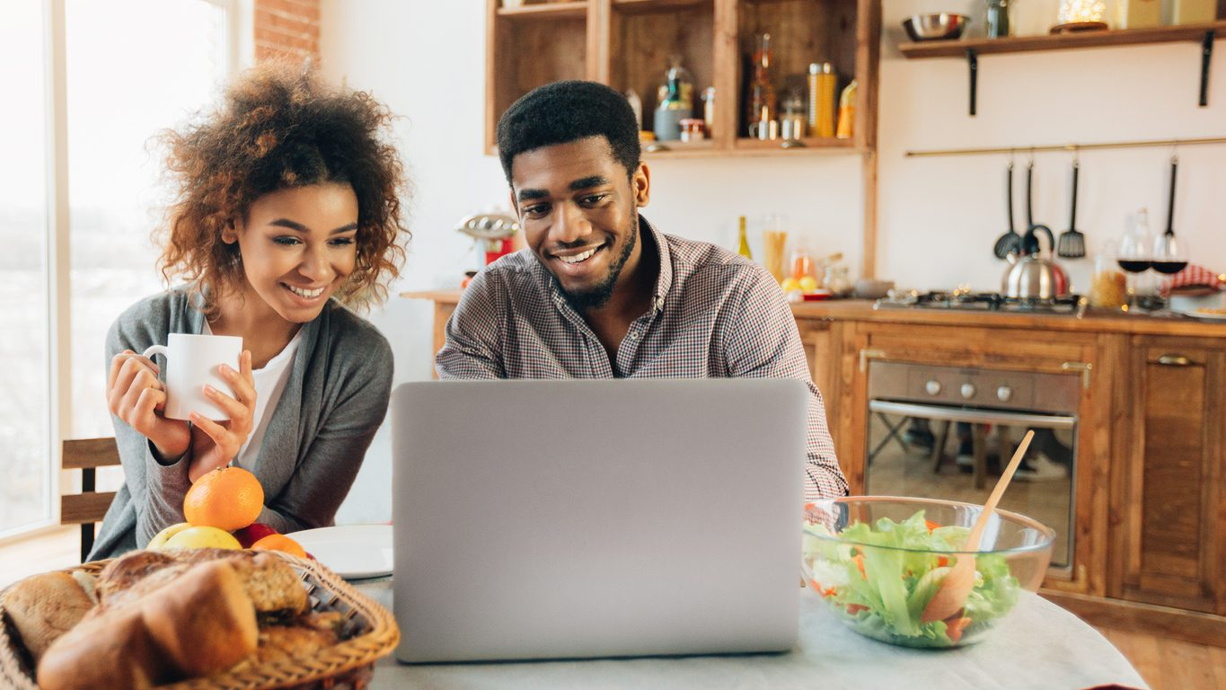 Man and woman sitting at kitchen table, looking at home insurance discounts on a laptop.