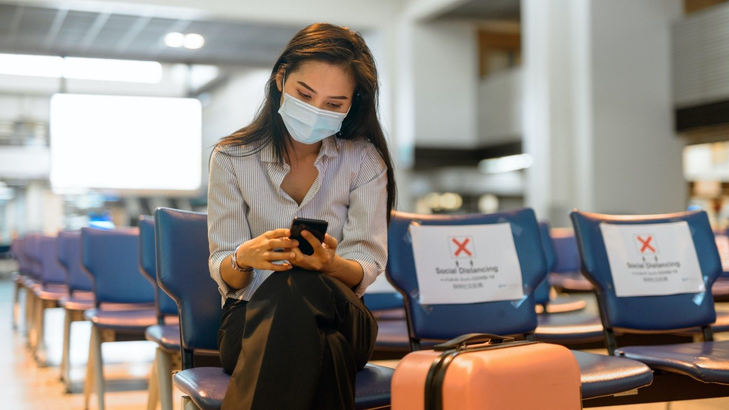 Woman sitting in airport terminal waiting area with mask on.