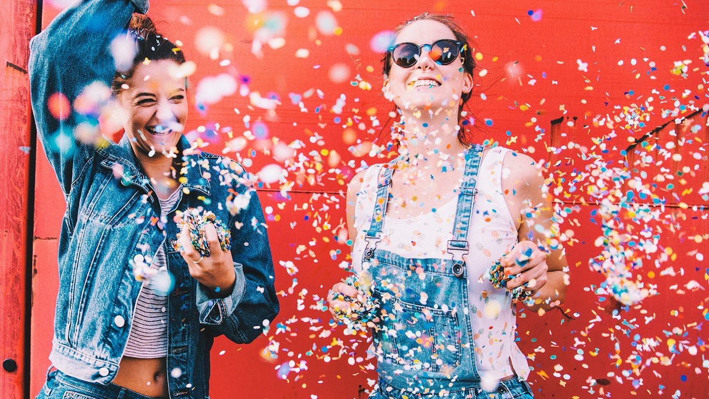 Young women with confetti celebrating savings, freebies and discounts