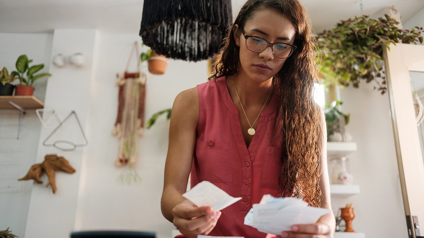 small business woman looking over bills and receipts