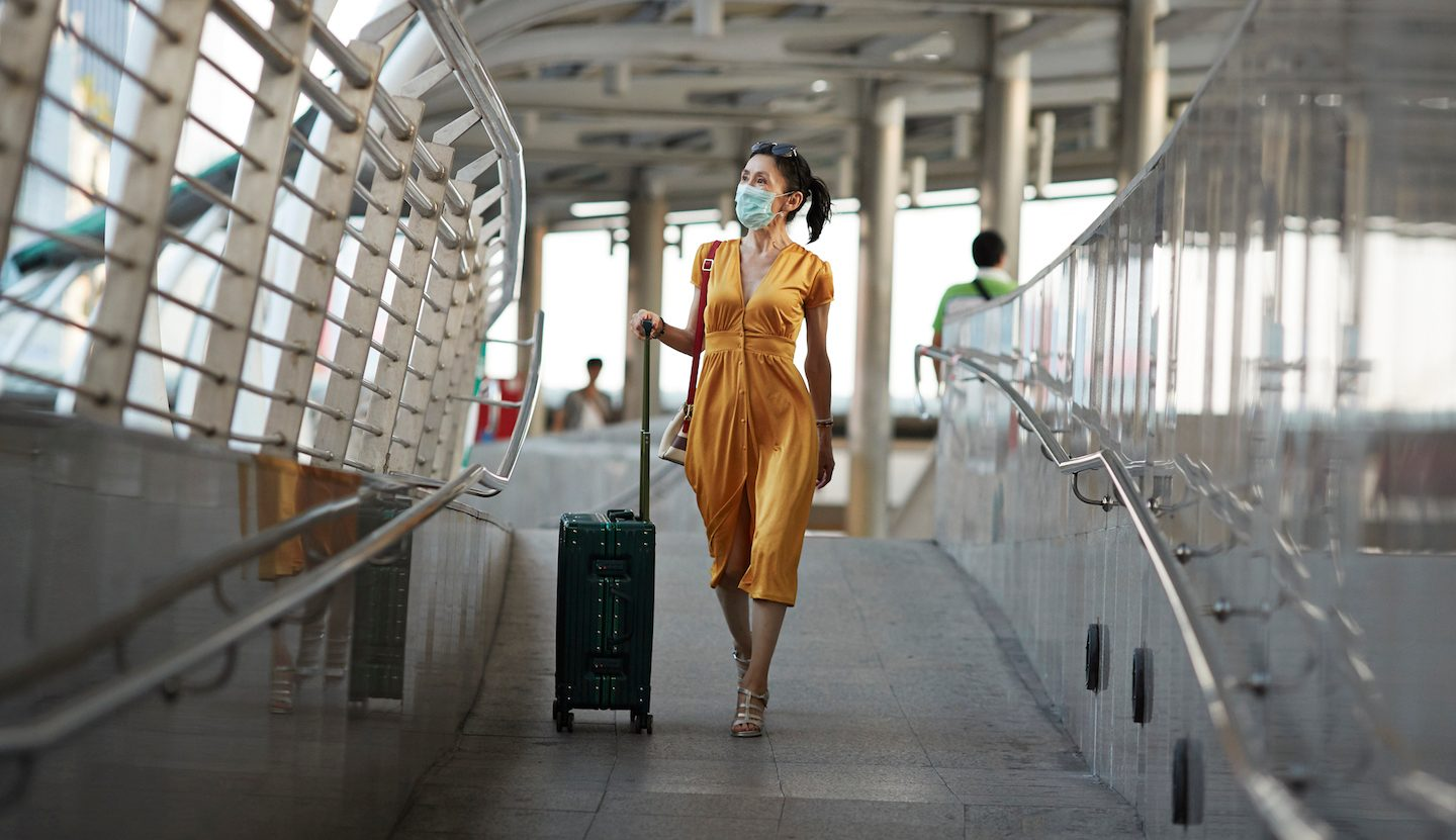 woman with mask travelling without insurance