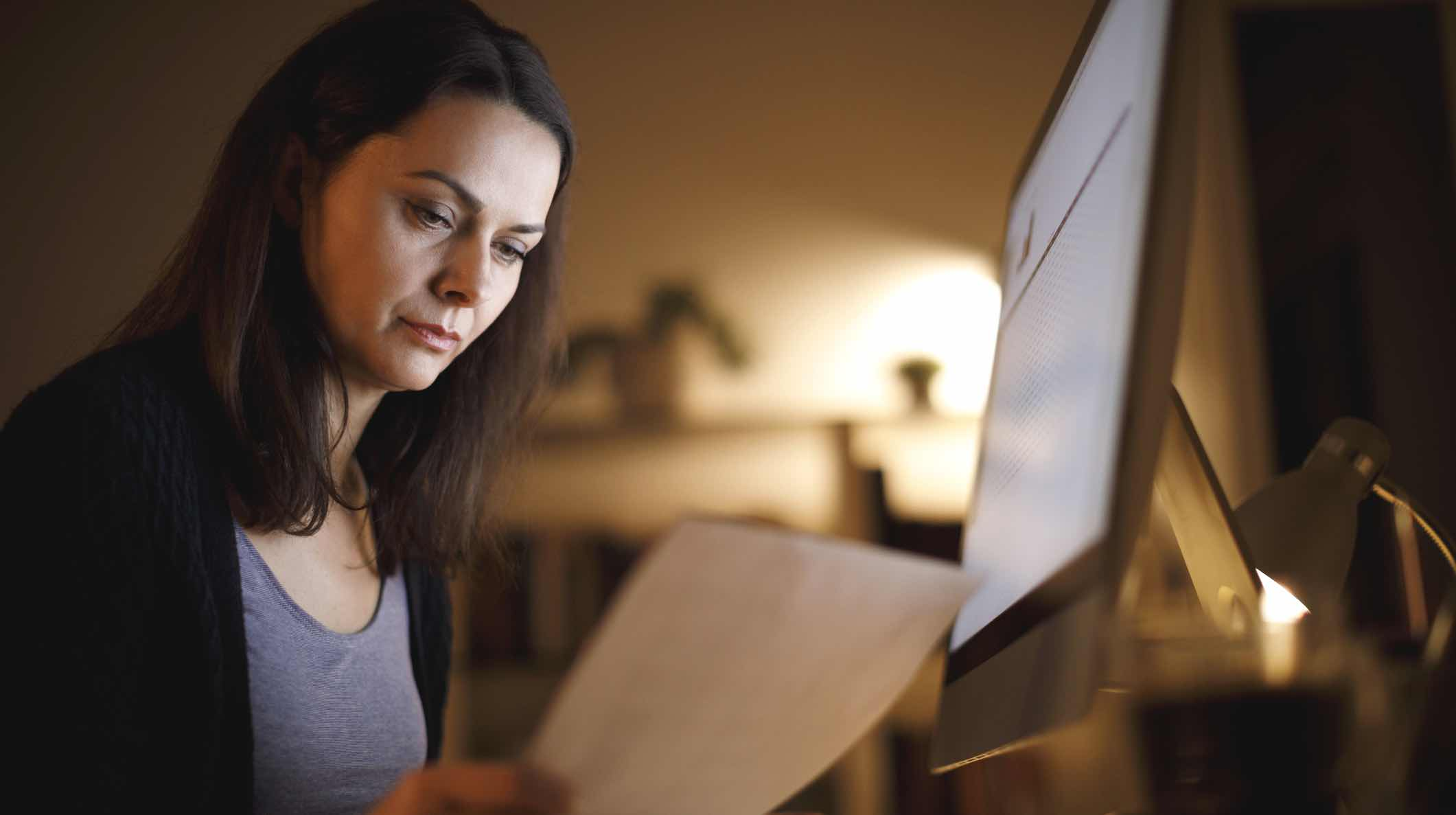 Woman checking bills, worried about early release of super