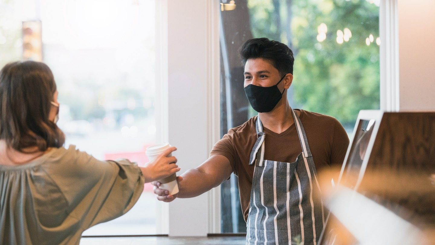 Australians spending more on eating out, barista wearing mask hands a cup of coffee to a woman also wearing a mask.