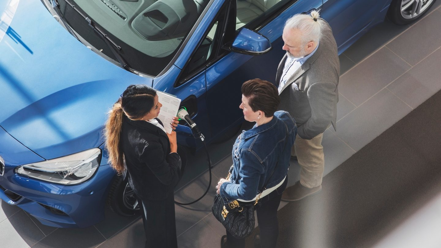 couple buying electric car from dealership