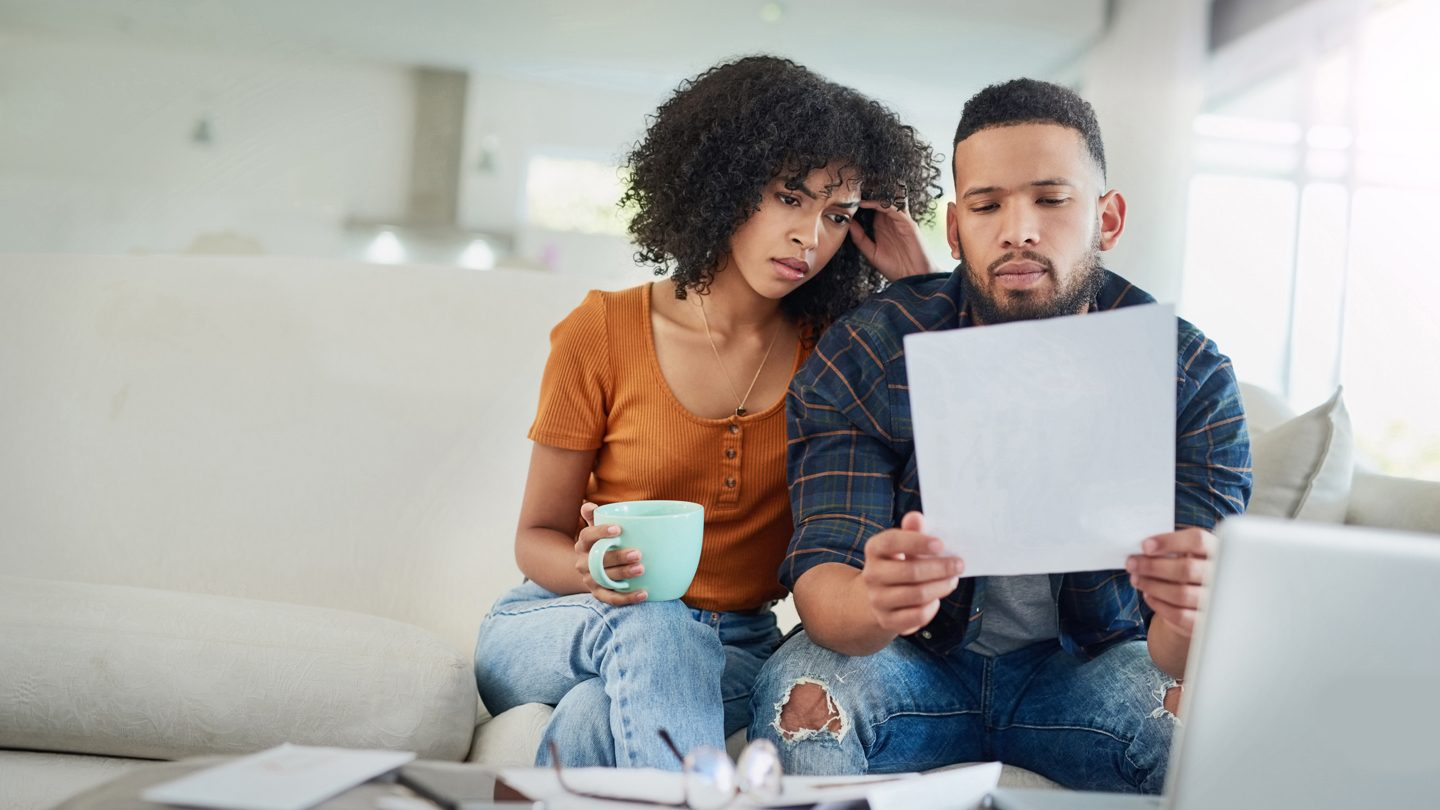 young first home buyers looking at bank statement