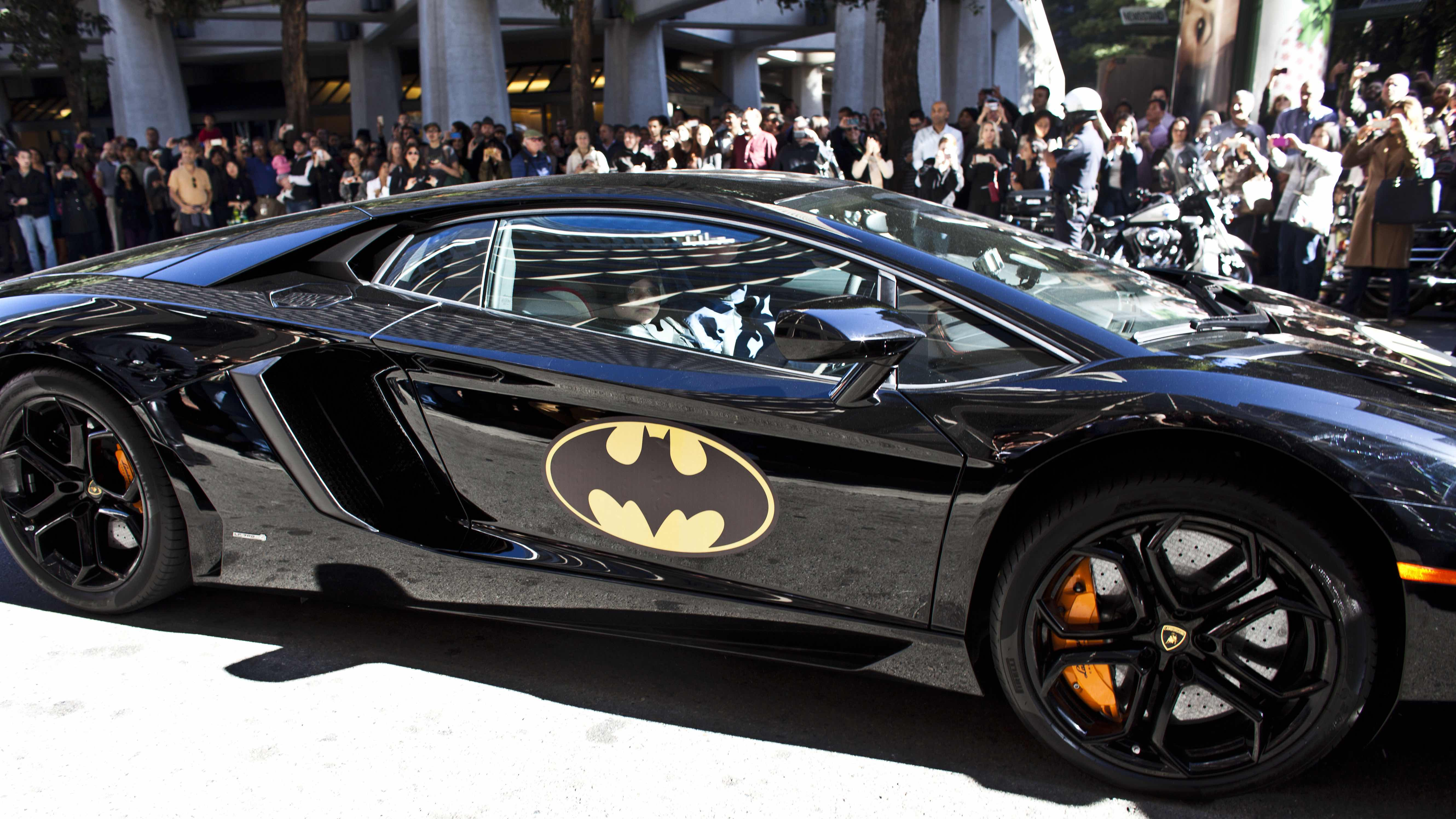 Batmobile driving past fans with car insurance