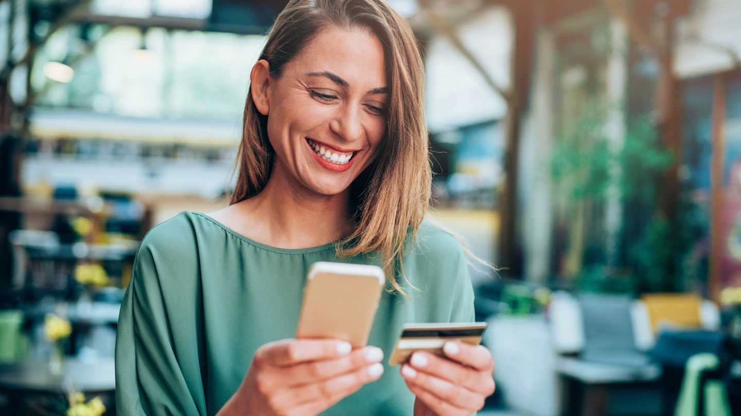 Happy female mutual bank customer looking at her phone and credit card