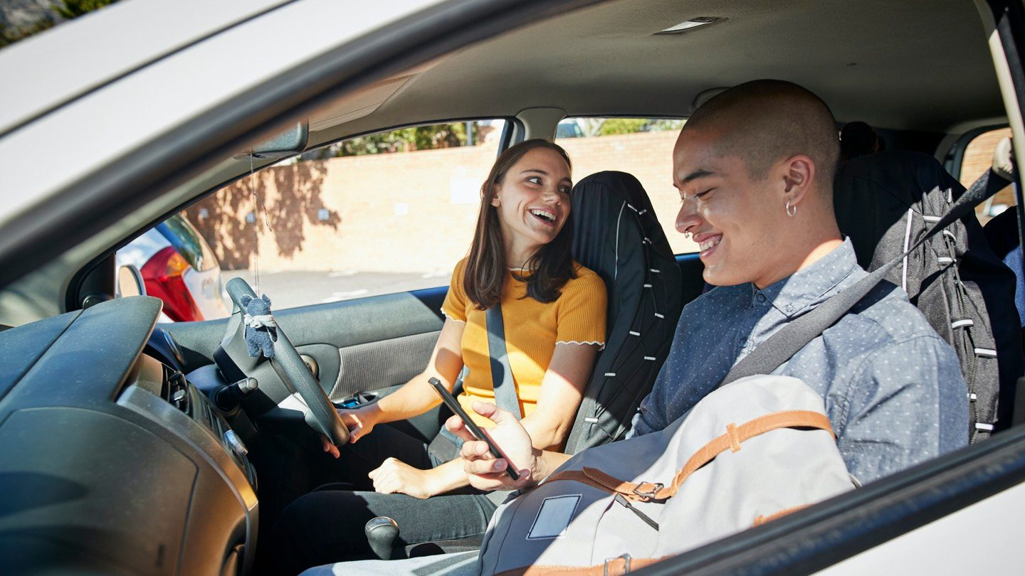 A young woman sits behind the steering wheel of a car. She smiles as she looks over her shoulder. A young man sits in the passenger seat, looking at his phone, smiling.