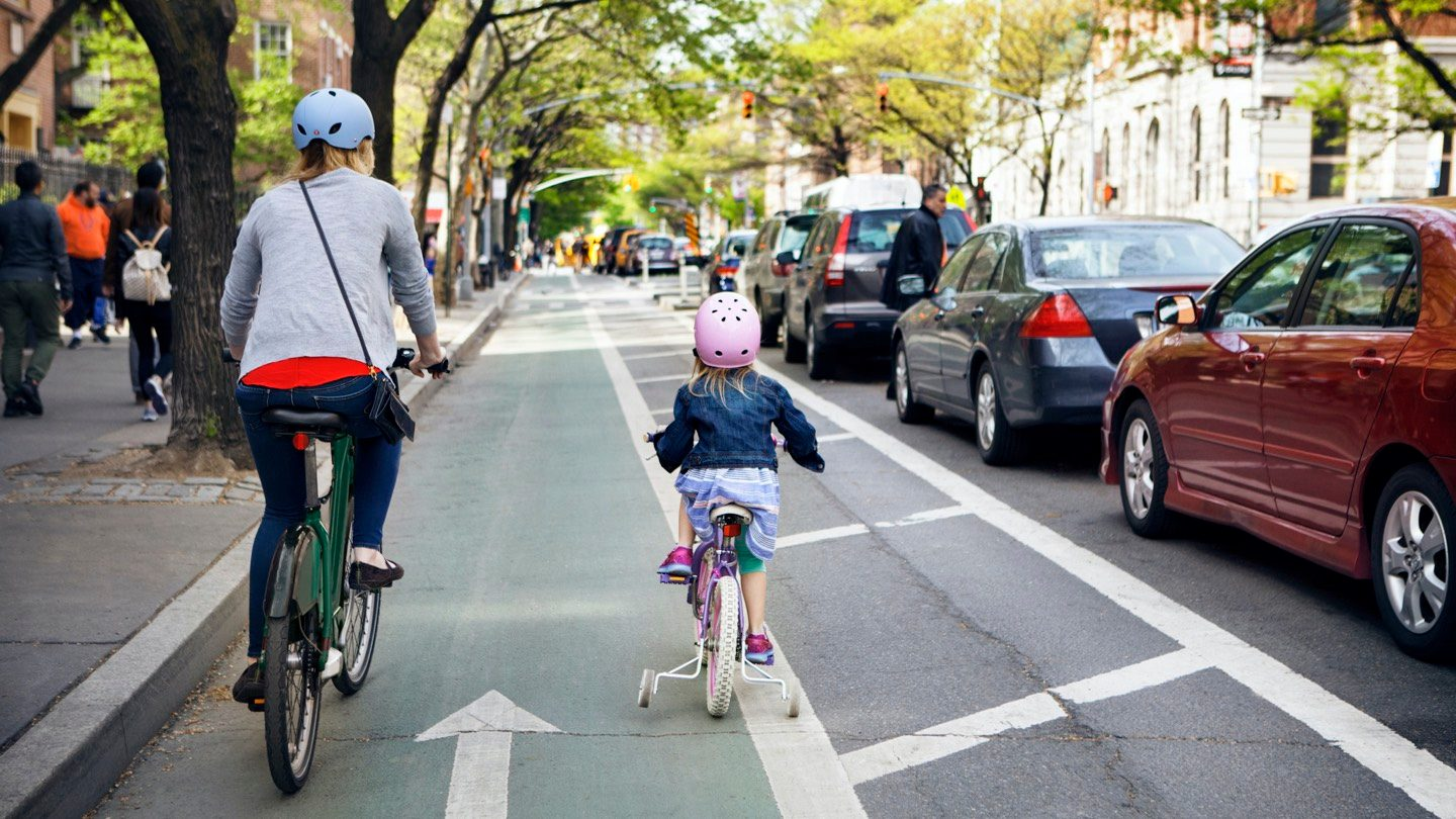 Rear view of mother and daughter cycling along a busy street with helmets on.