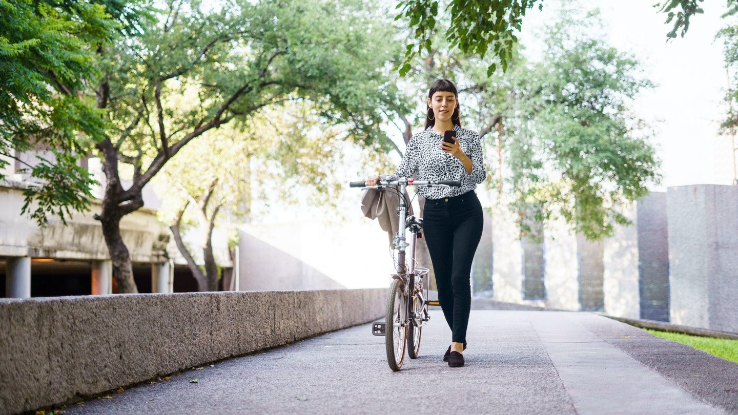 Woman walking along tree-lined pathway with bicycle. She is looking at term deposits on her mobile phone.