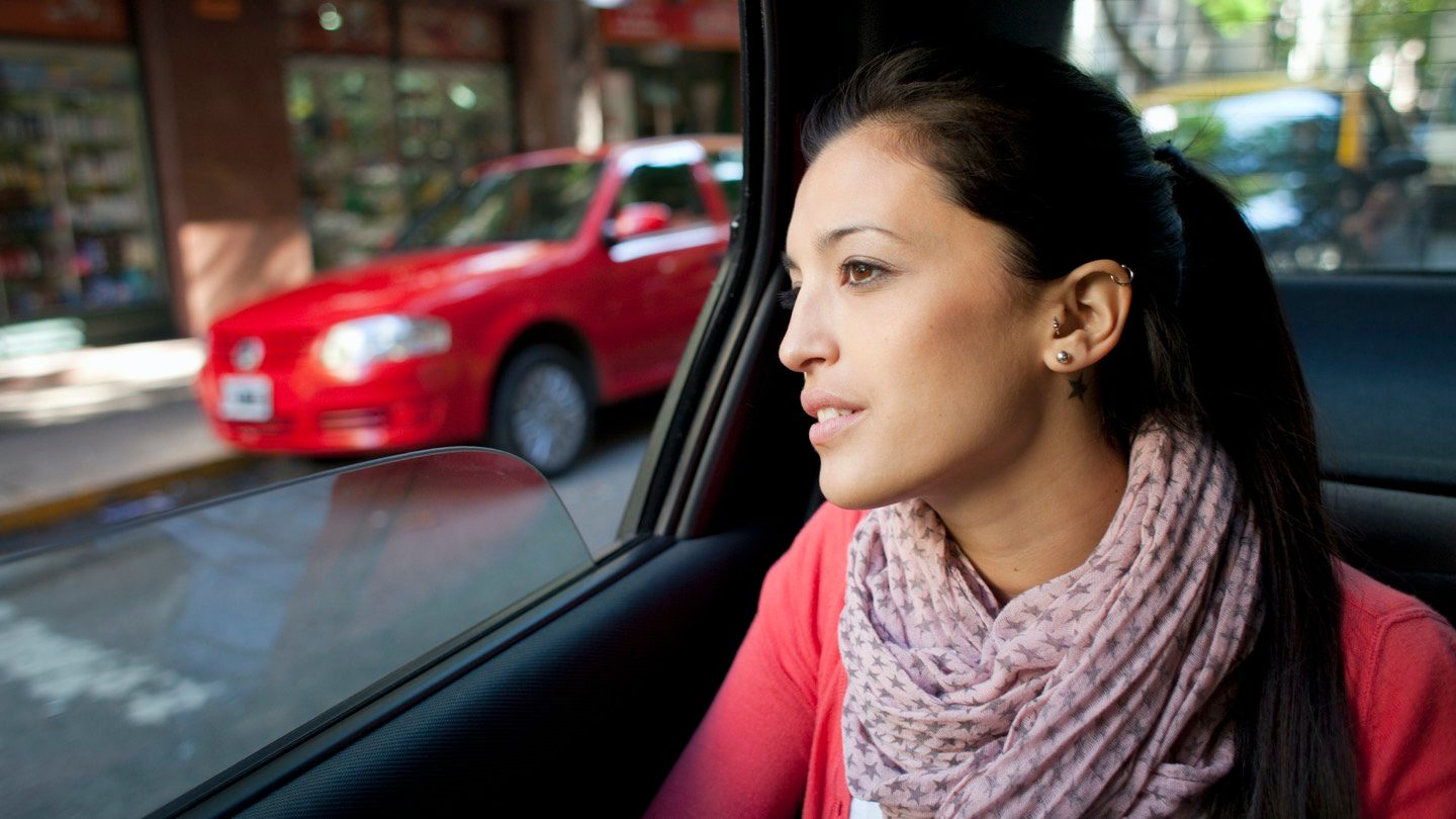 Woman sitting in the back of a car, thinking about car insurance.