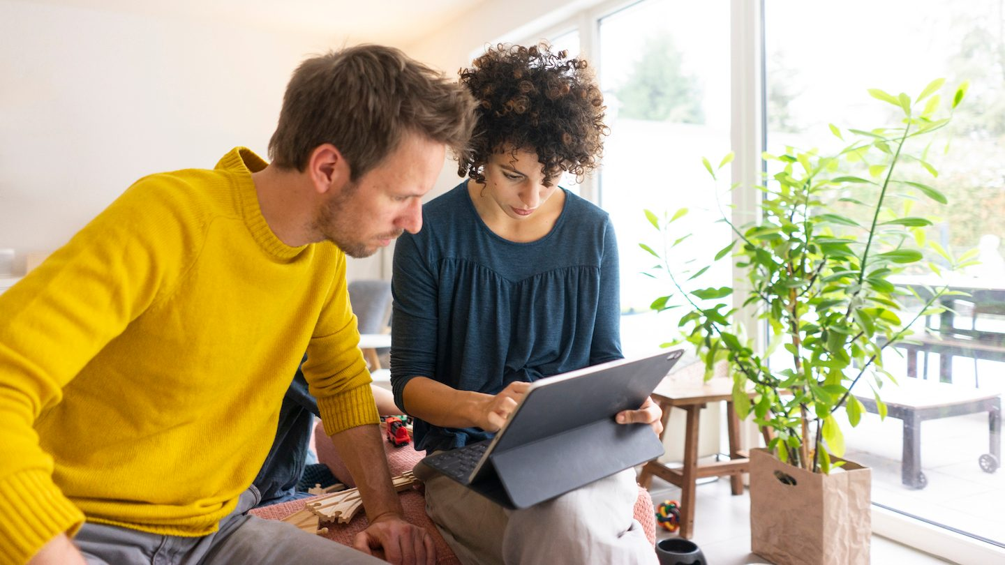 couple looking up credit cards on tablet