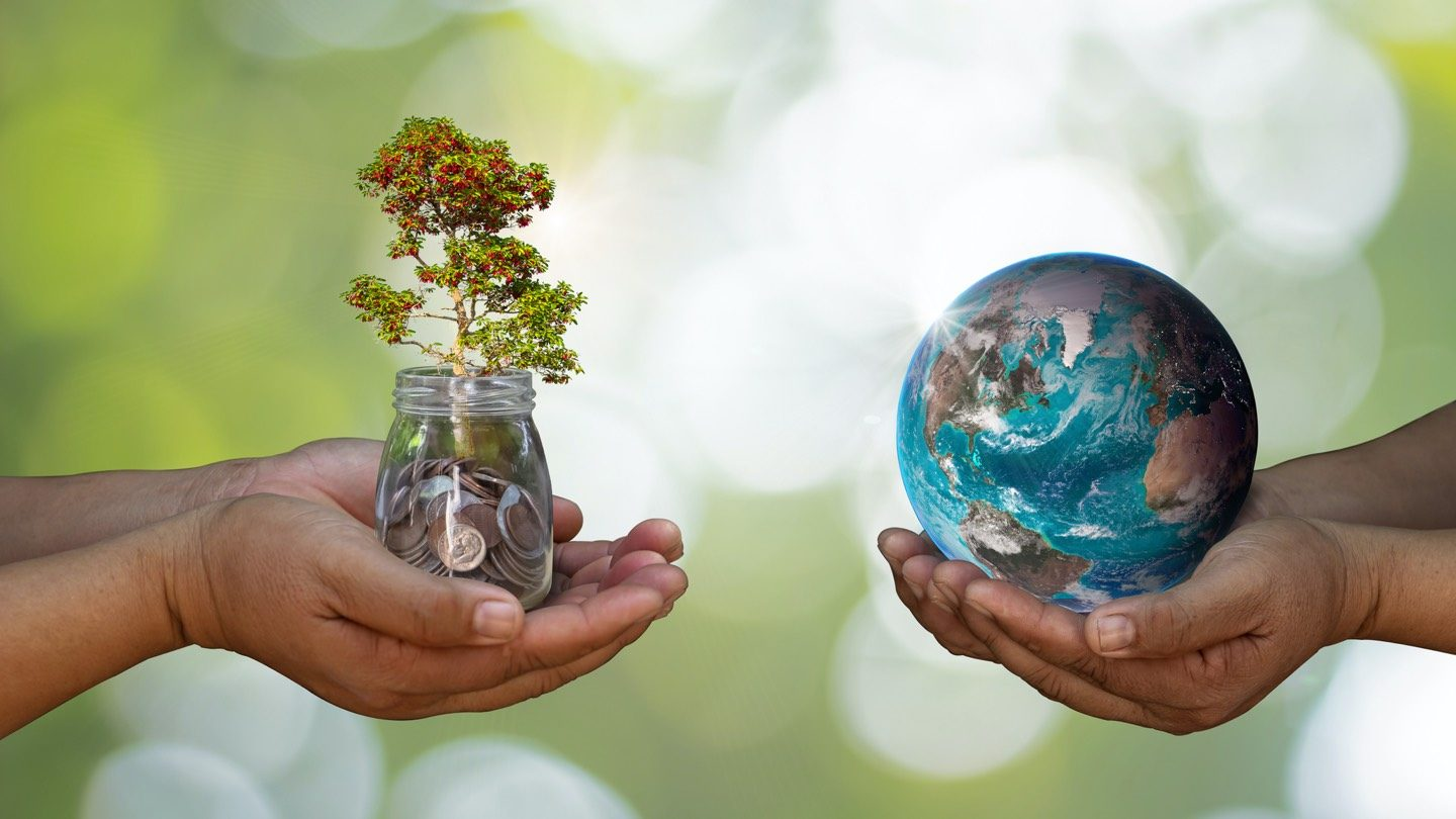 Two pairs of hands, one holding a jar of coins and mini trees, the other holding a globe to symbolise divestment.