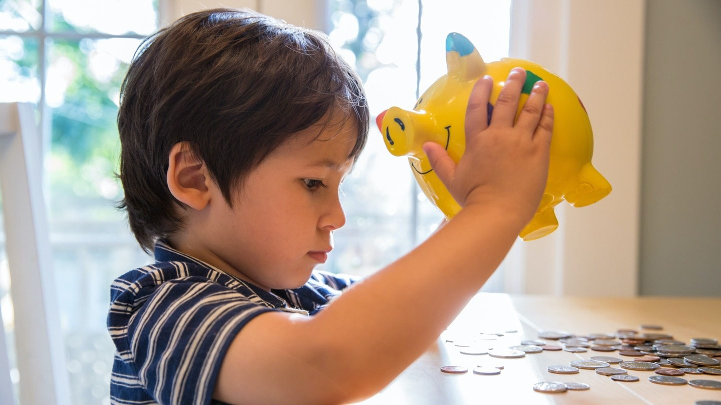 Little boy empties dollars and cents out of a piggy bank onto a table.