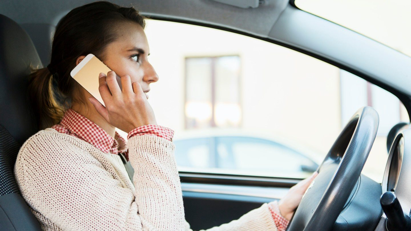 Woman talking on phone while driving.