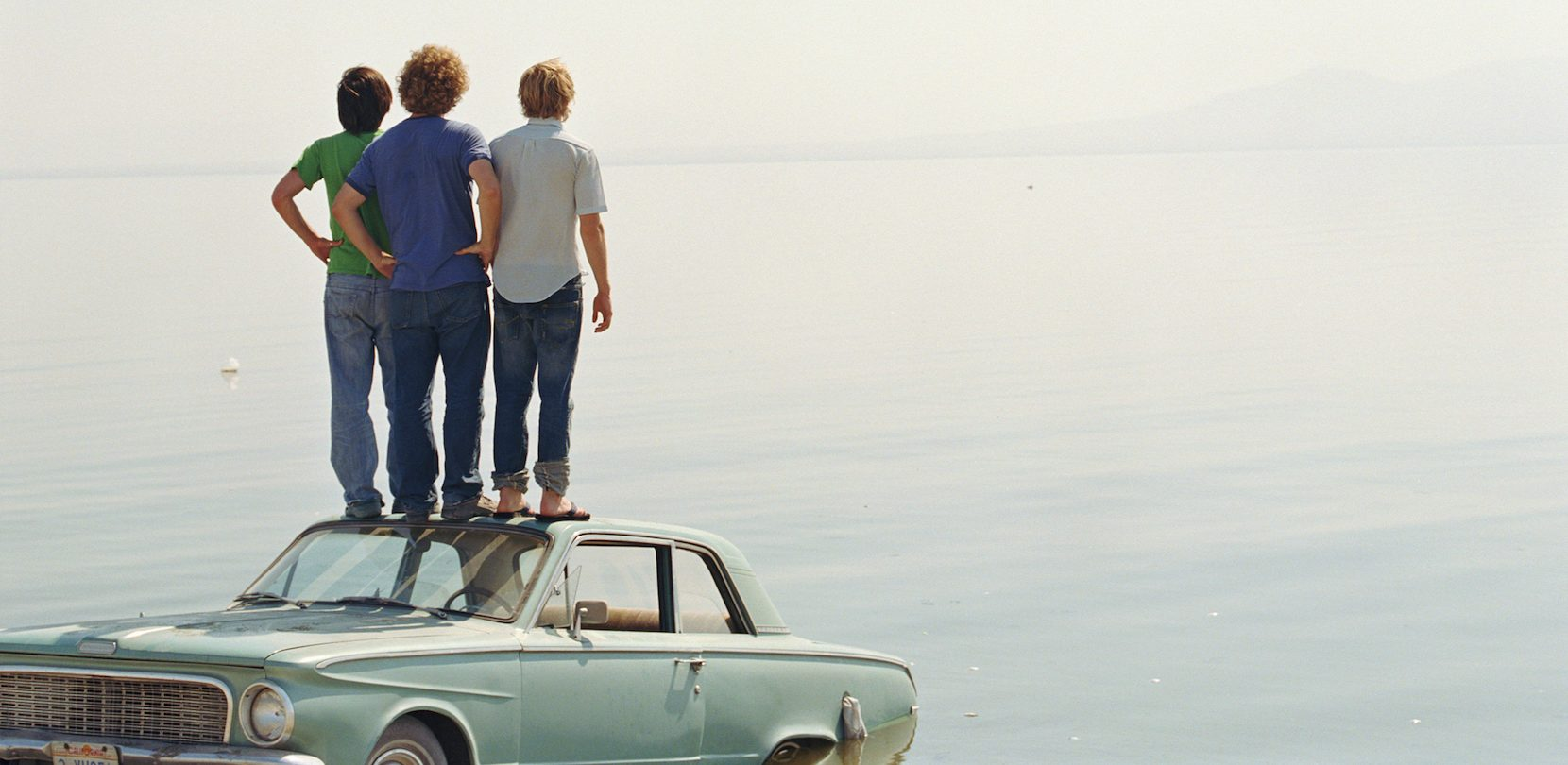 three men standing on car bought with car loan