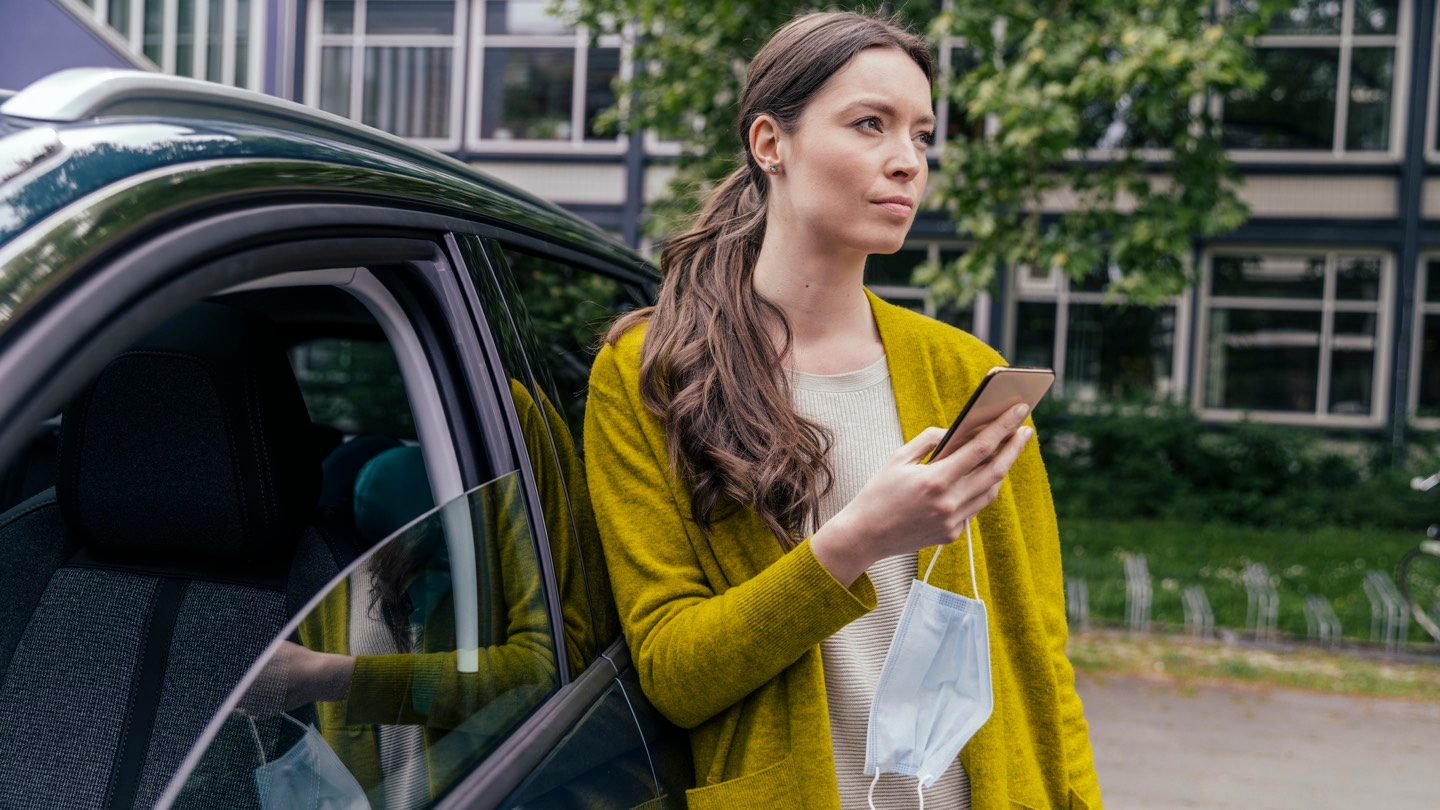 Woman standing next to car, comparing car insurance on her phone.