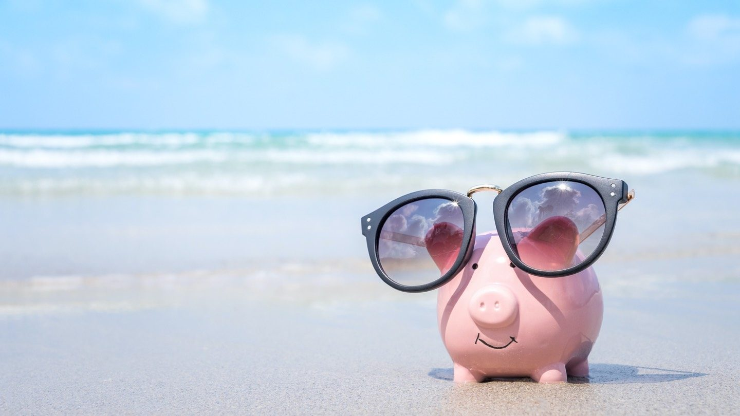 Piggy bank sitting on a beach with sunglasses on.