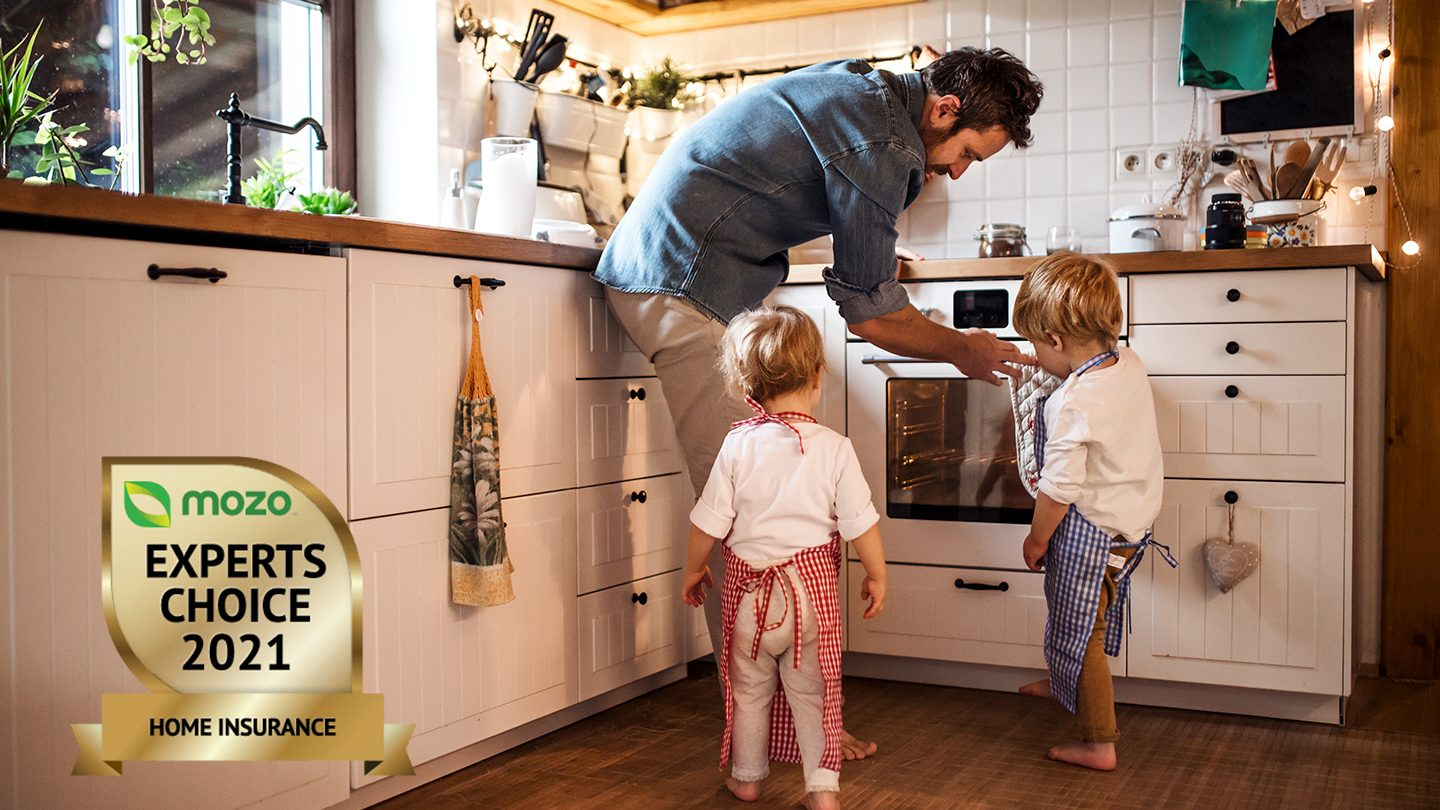 Parent showing children something in kitchen after taking out a top home insurance policy.