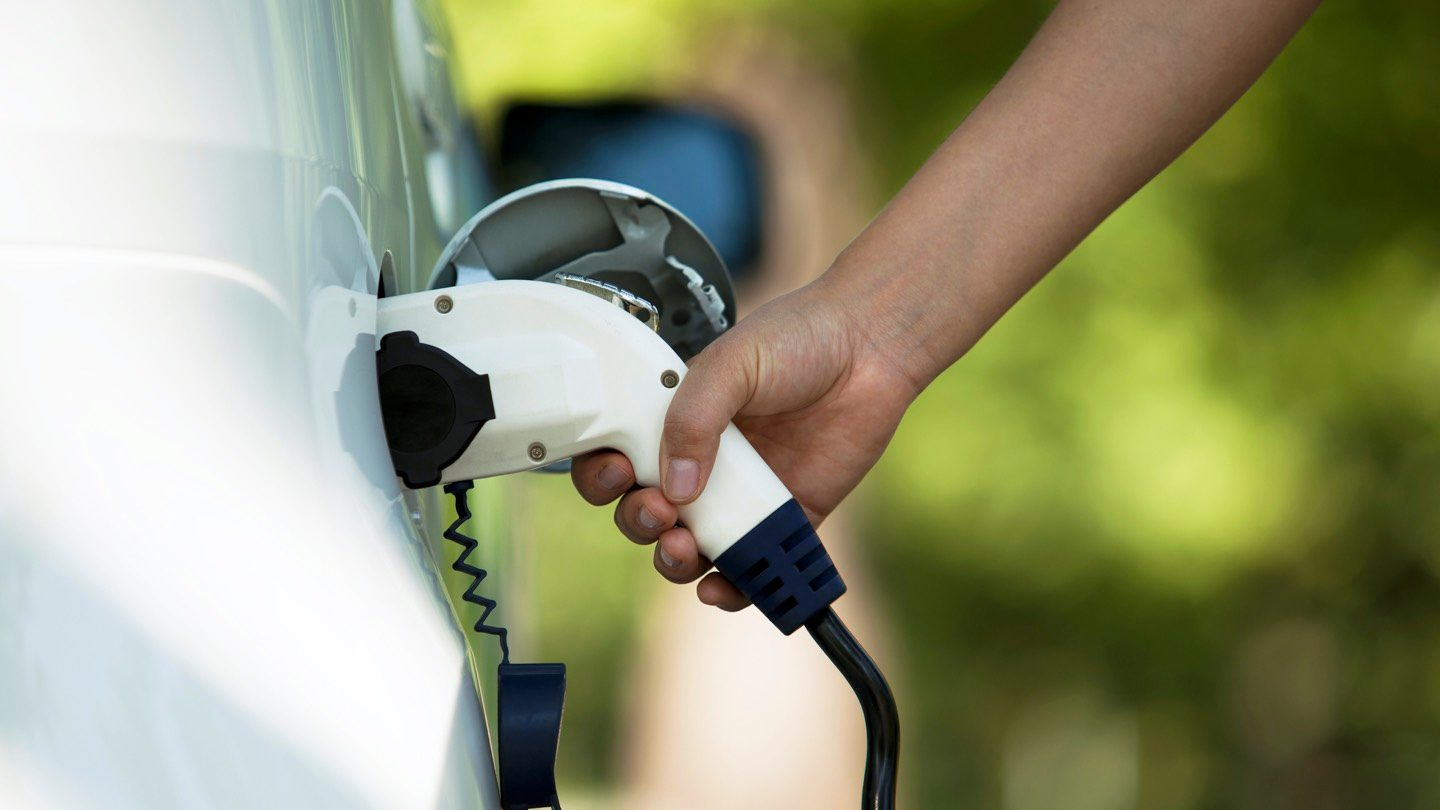 Person charging electric vehicle.