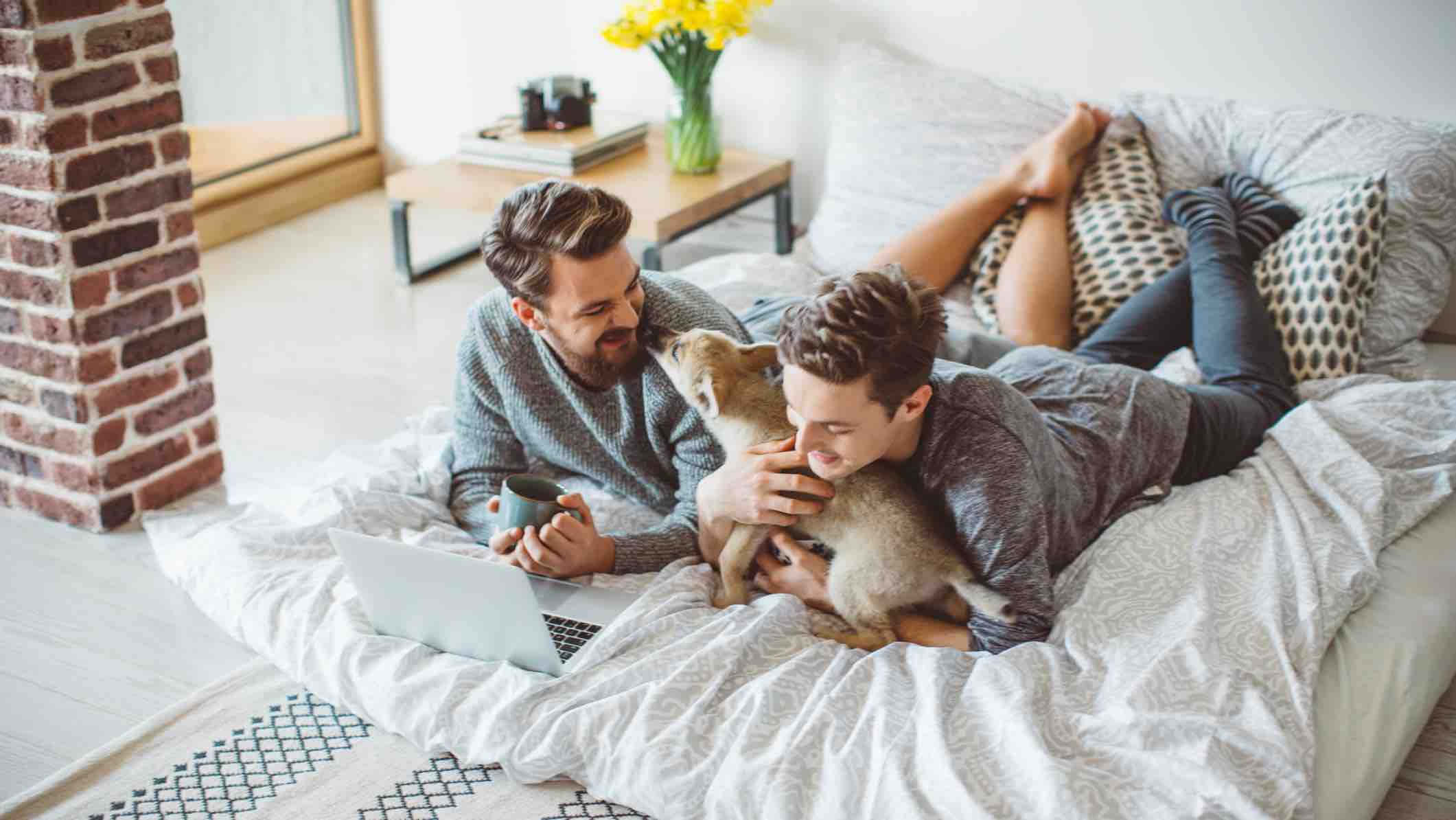 Couple laying on bed with dog researching home loans