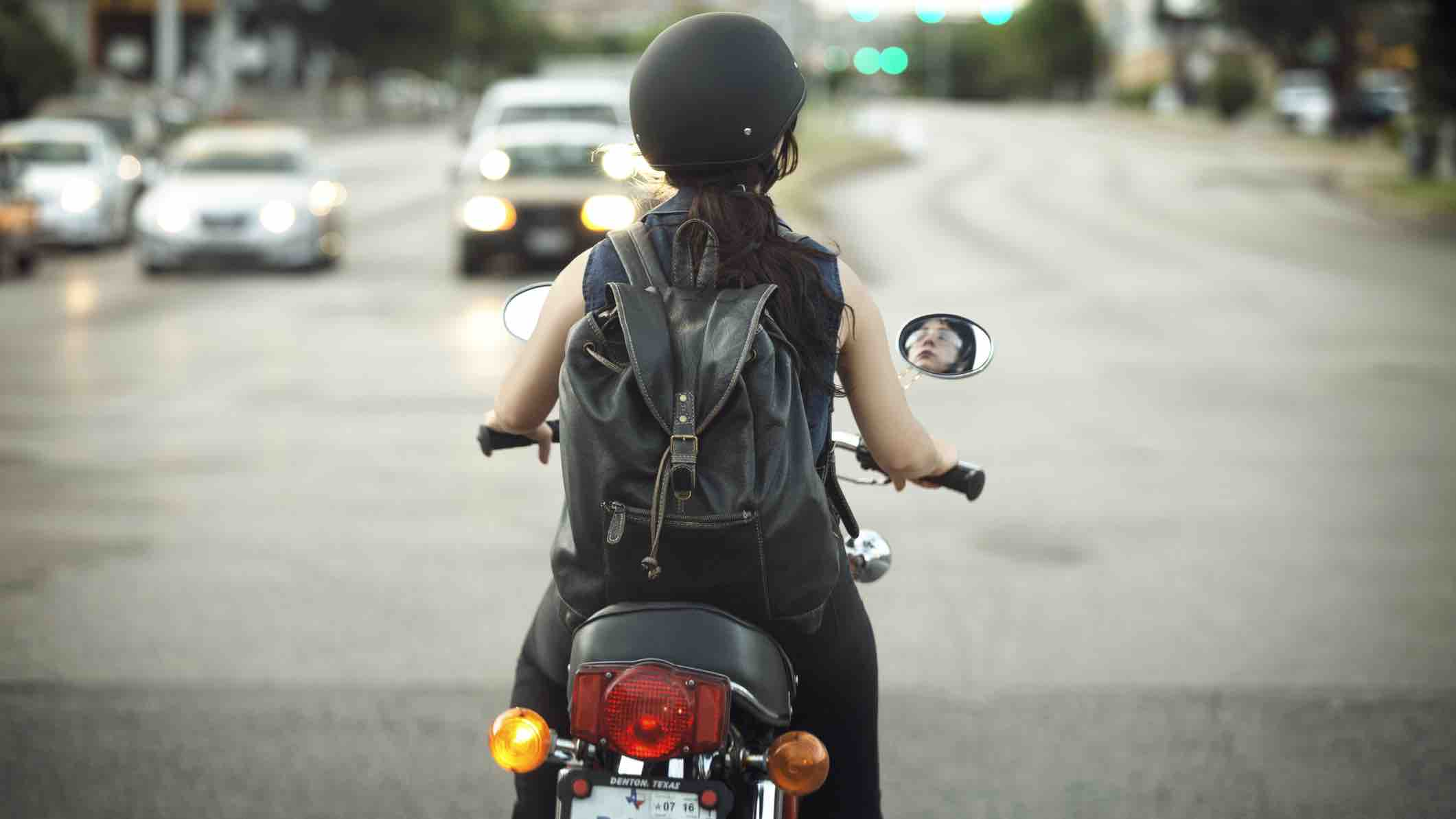 Person on motorcycle looking at cars
