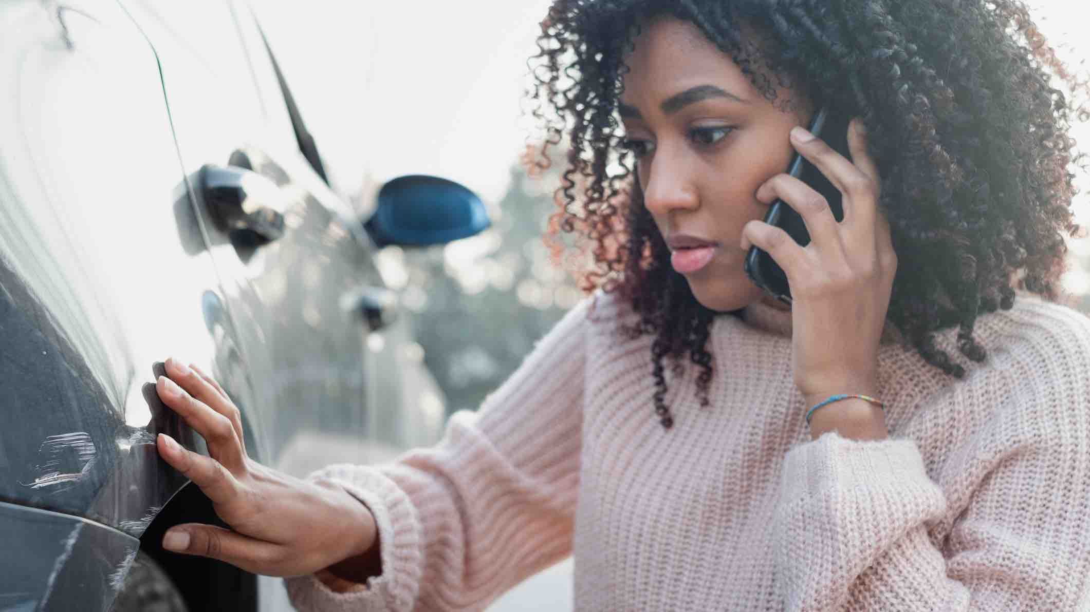 Woman calling her car insurer after an accident