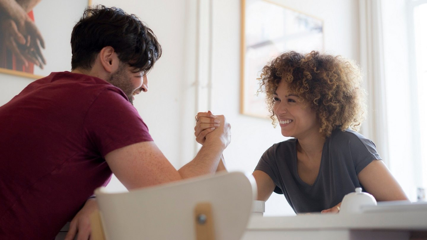 Young homeowner couple arm wrestling