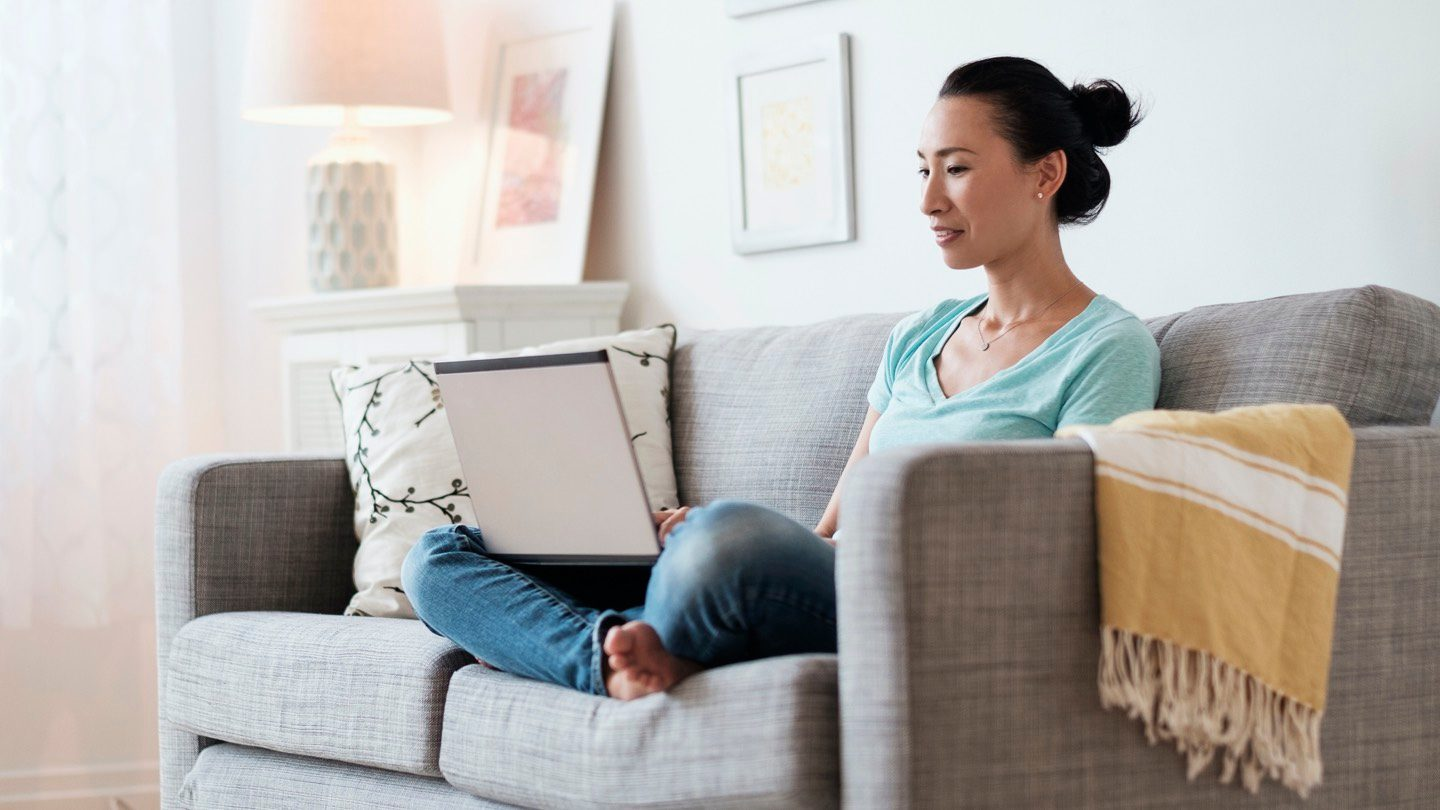 Woman sitting on sofa, looking at bank accounts on laptop.