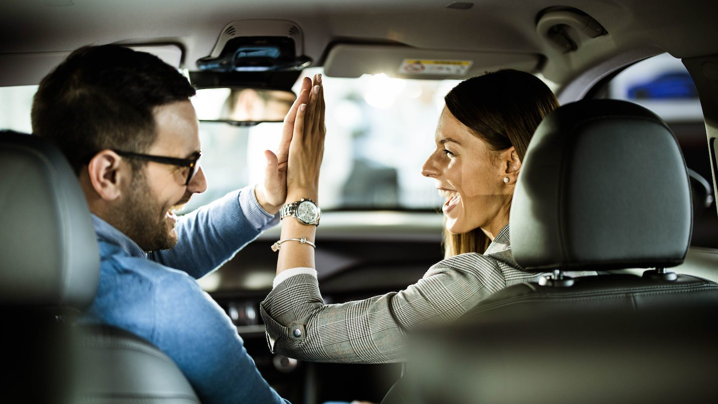happy couple high five because bought car with vehicle finance