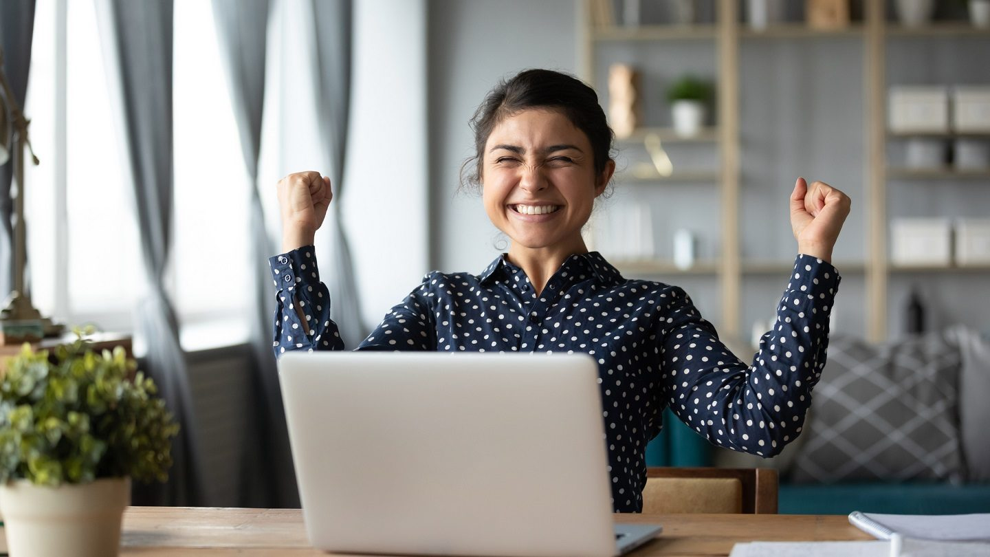 Woman celebrating investors home loan cuts in front of laptop screen