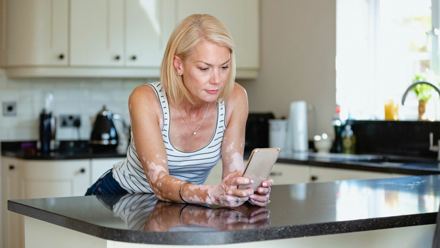 Woman leans on kitchen counter, looking at term deposits on her phone.