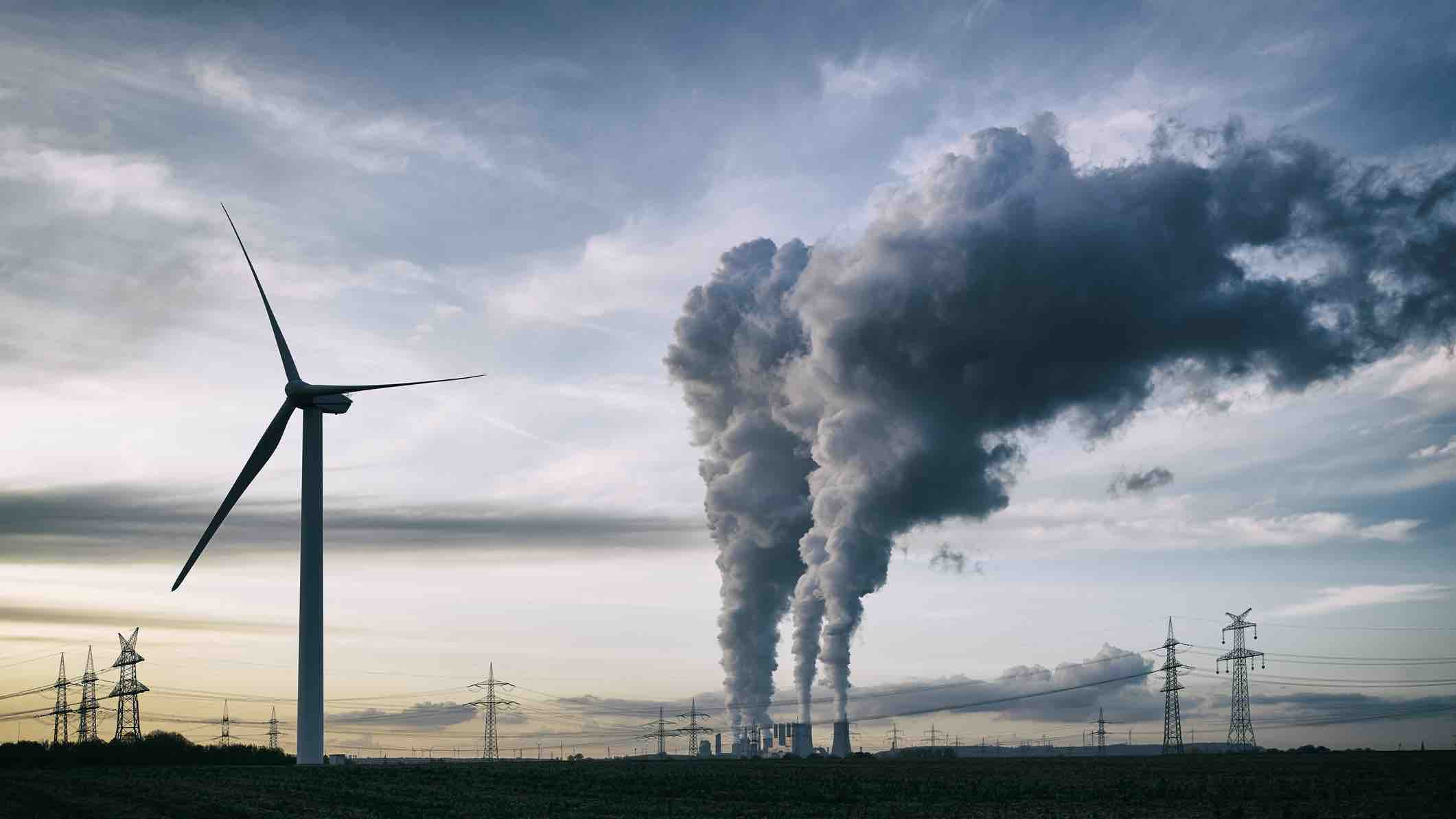 Wind turbines and smoke from a power plant with electrical lines in the distance.