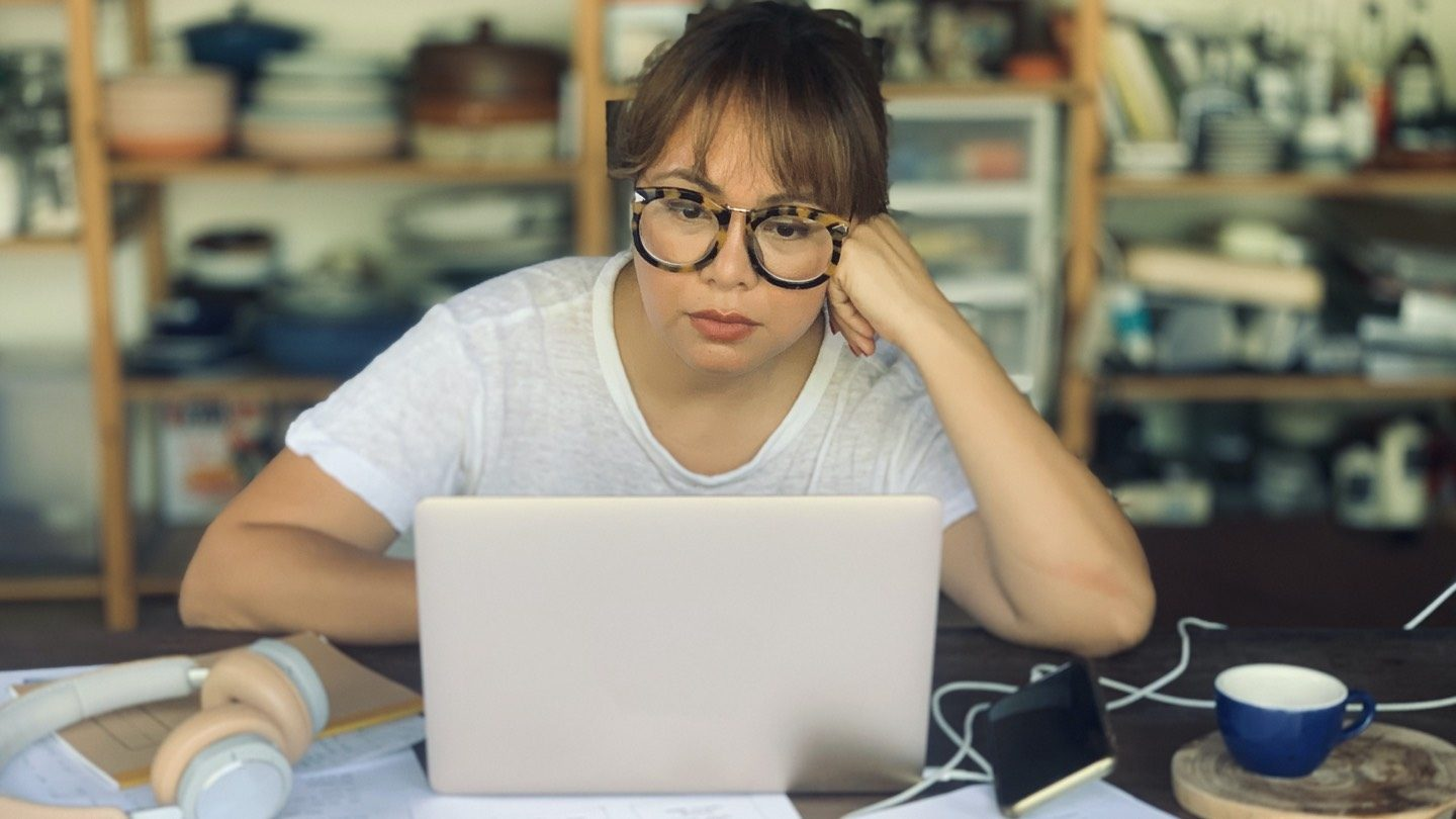 Woman sitting at table, looking up car insurance on laptop.