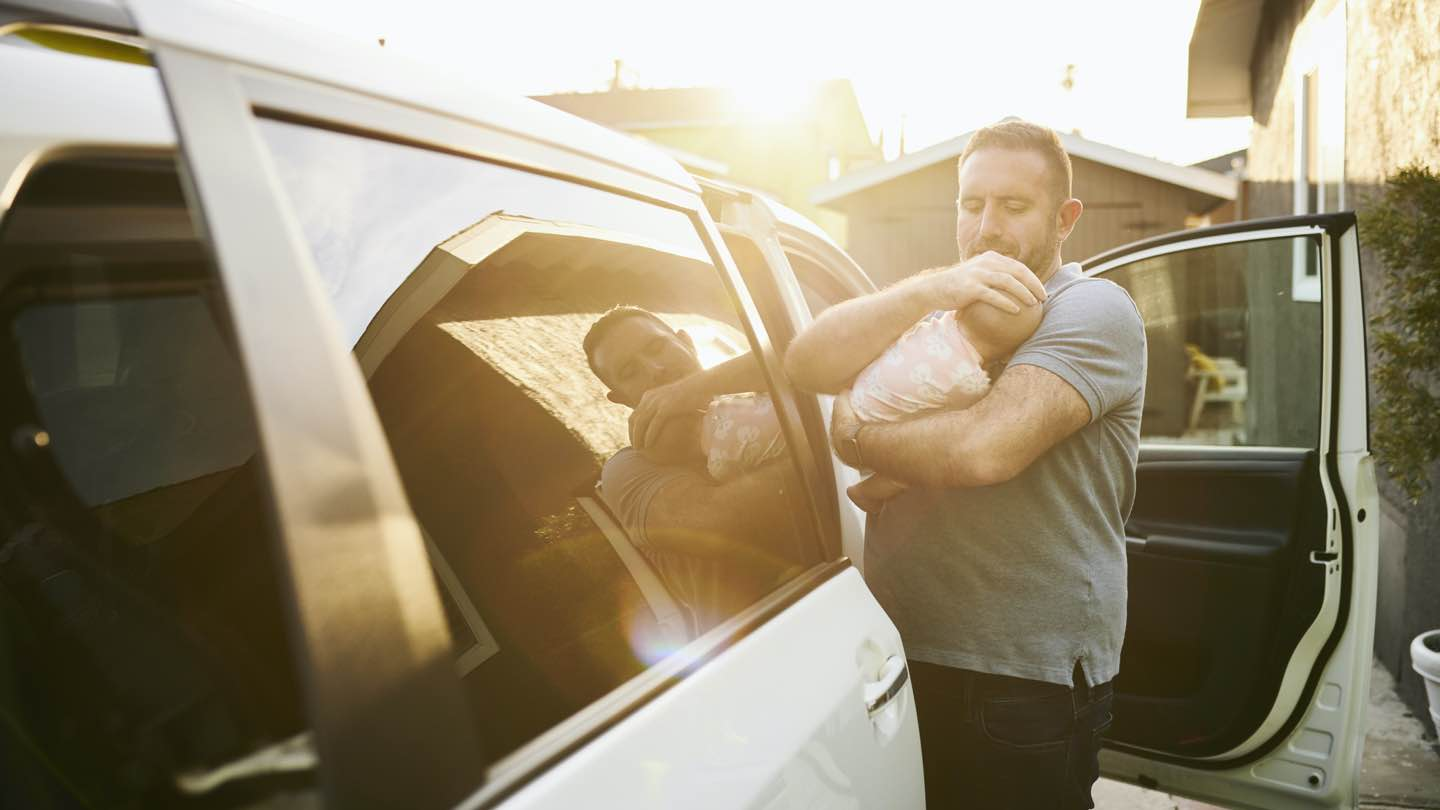 Father takes baby out of car after long roadtrip.