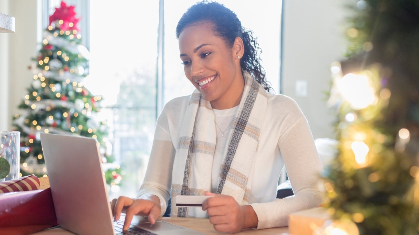 Woman sending money overseas on laptop with Christmas tree in the background