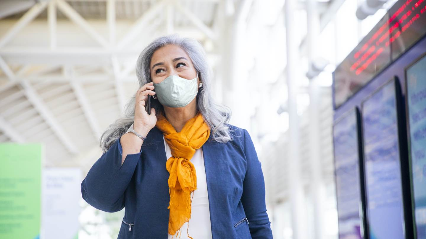 Hispanic woman with grey hair, face mask, blue blazer and orange scarf talks on mobile while standing in the airport.