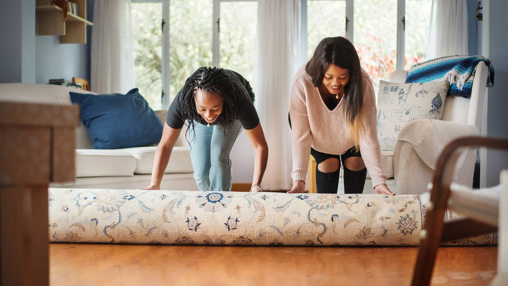 Two women rolling out a rug after buying and moving into their first home.