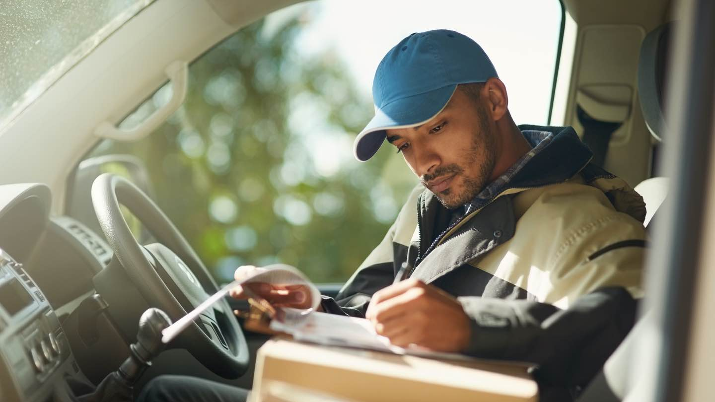 A delivery man sitting in a car wearing a blue cap checks parcel delivery information.