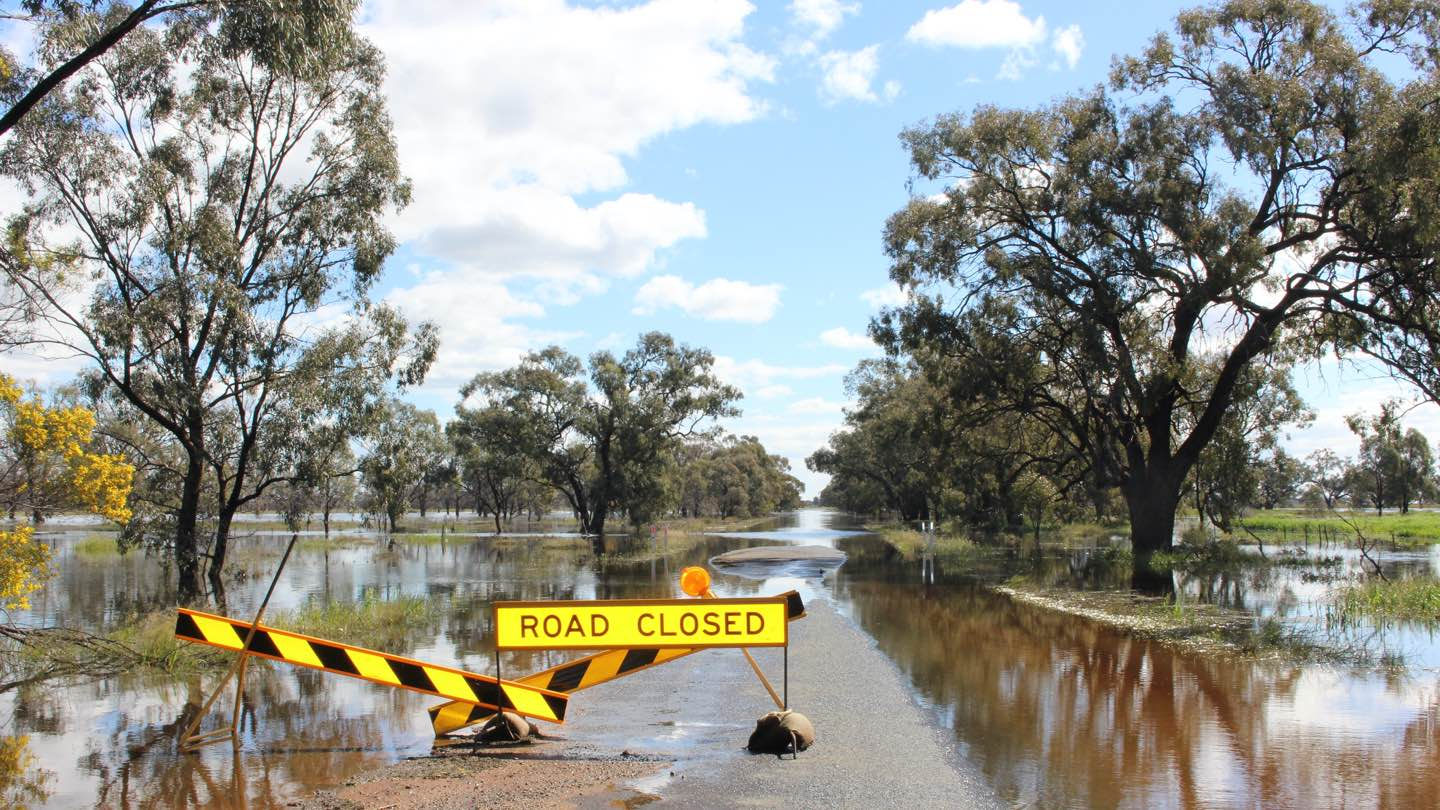 Flooded Australian landscape with sign reading 'road closed'.