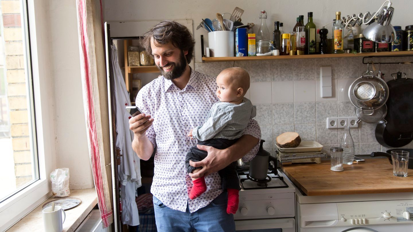 Man standing in cluttered kitchen holding a baby looks at his phone, smiling.