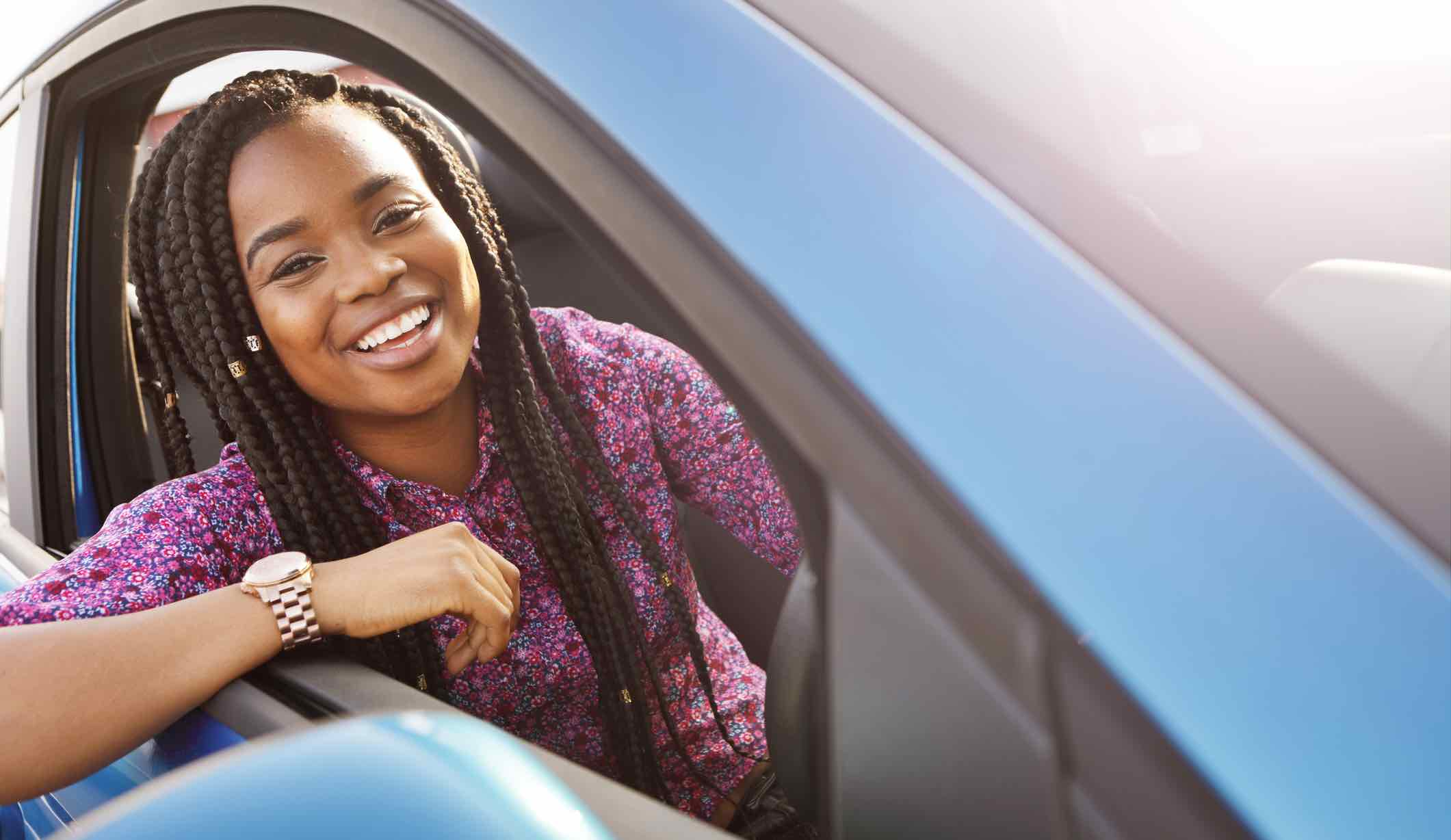 Young driver sitting in a car, considering CTP options and prices.