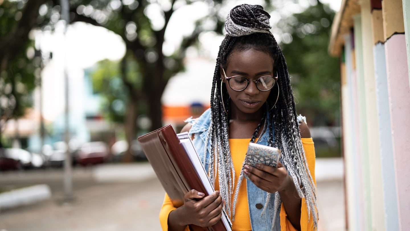 A woman walks down the street holding folders in one hand and her phone in the other.