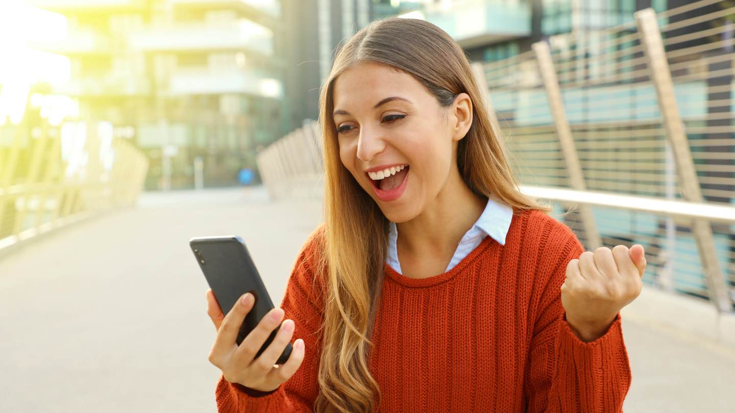 Blonde-haired woman with red jumped stands looking at her phone, smiling.
