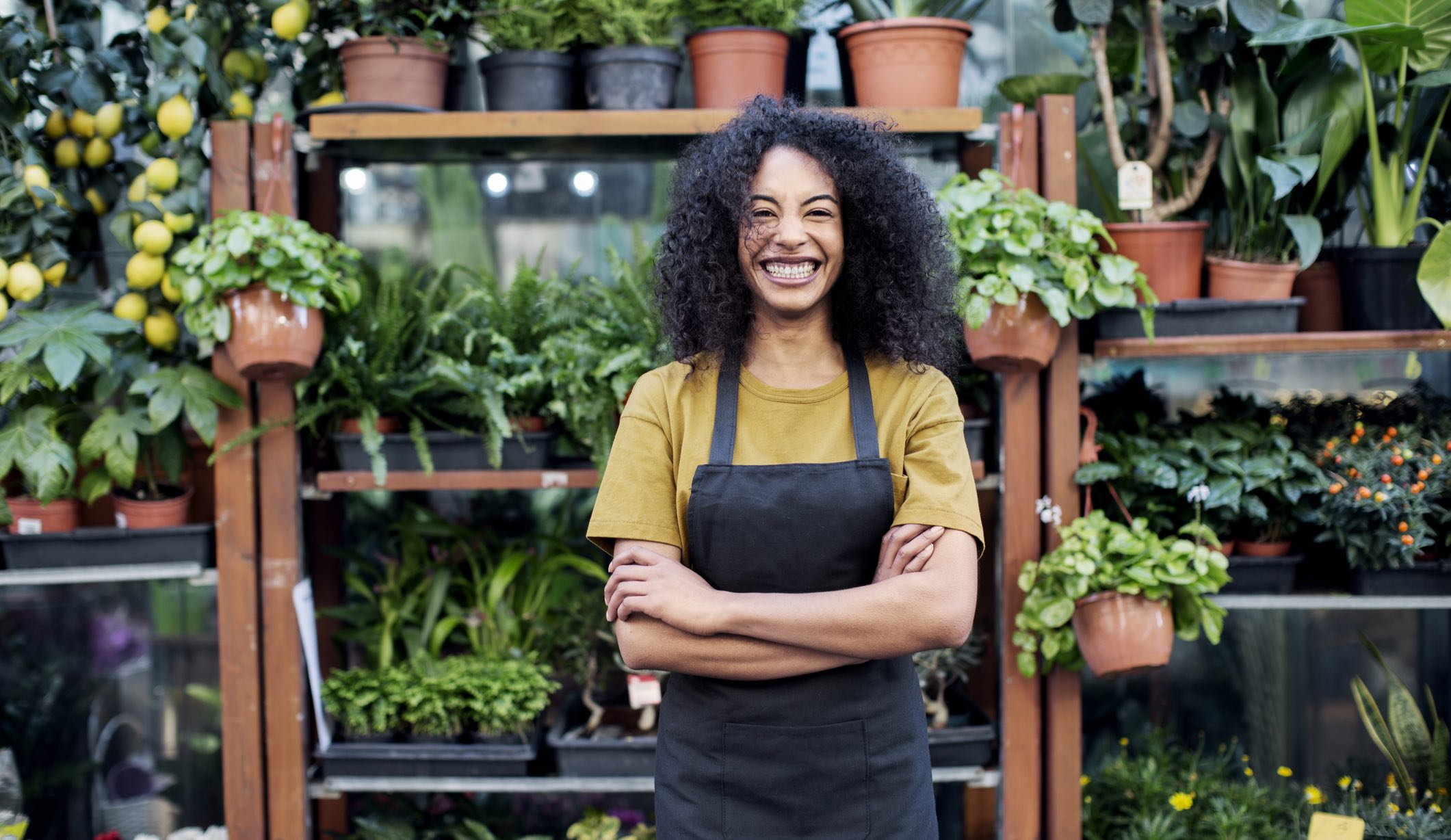 Smiling young person standing in front of a plant shop in an apron, thinking about savings interest rates.