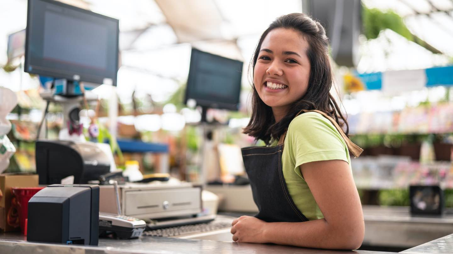 Young woman stands at checkout, smiling